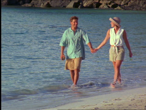 slow motion couple with shorts holding hands walking along surf at beach / st. john / virgin islands - shorts stock-videos und b-roll-filmmaterial