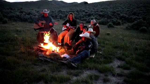 slow motion cowboy family campfire cookout - differential focus stock videos & royalty-free footage