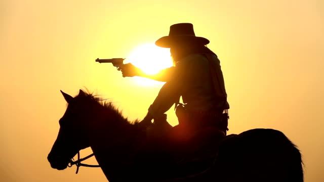 馬に乗っているスローモーションカウボーイと日没に銃を描く - 銃点の映像素材/bロール