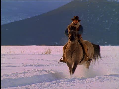 slow motion cowboy riding horse in snow / mtns in background - pflanzenfressend stock-videos und b-roll-filmmaterial