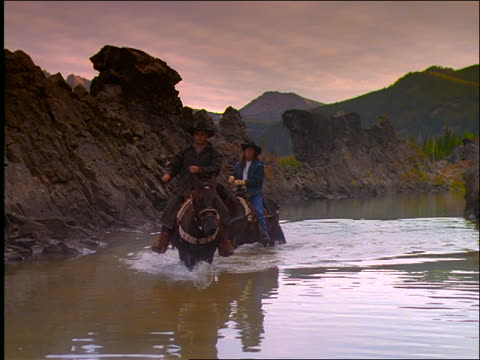 slow motion cowboy + woman riding horses in lake with mountains in background / oregon - cowboyhut stock-videos und b-roll-filmmaterial