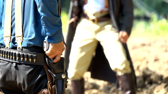 slow motion cowboys zeichnen gun shooting at enemy - cowboy stock-videos und b-roll-filmmaterial