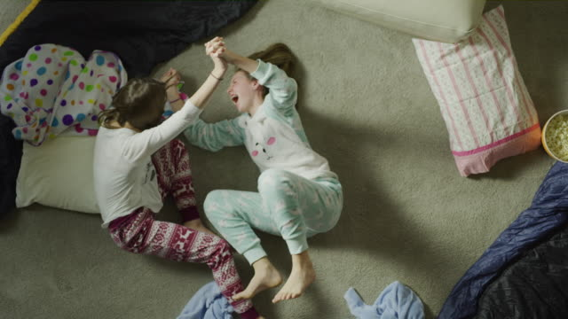 Slow motion crane shot of girls laughing and playing on floor during sleep over / Cedar Hills, Utah, United States