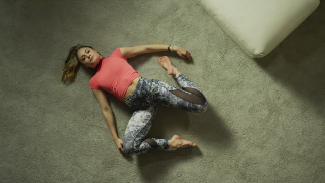 stockvideo's en b-roll-footage met slow motion crane shot of teenage girl laying on floor and stretching legs / cedar hills, utah, united states - flexibiliteit