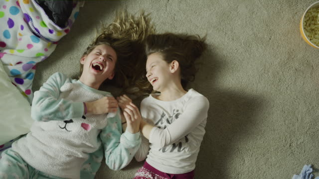 slow motion crane shot zoom out of girls laughing on floor at sleep over / cedar hills, utah, united states - ridere video stock e b–roll