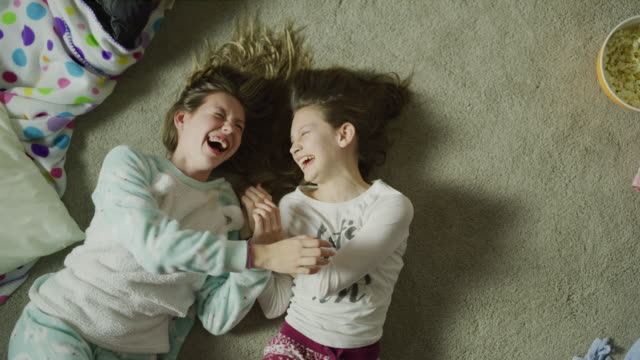 slow motion crane shot zoom out of girls laughing on floor at sleep over / cedar hills, utah, united states - roll over stock videos and b-roll footage
