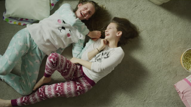 slow motion crane shot zoom out of girls laughing on floor at sleep over / cedar hills, utah, united states - slumber party stock videos and b-roll footage