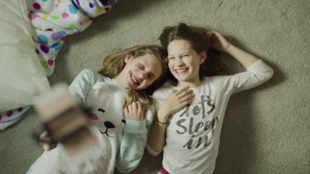 Slow motion crane shot zoom out of girls laying on floor using selfie stick / Cedar Hills, Utah, United States