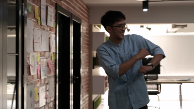 slow motion creative asian man designer dancing in modern office,see good idea and news on data board and happy dance - good news stock videos & royalty-free footage