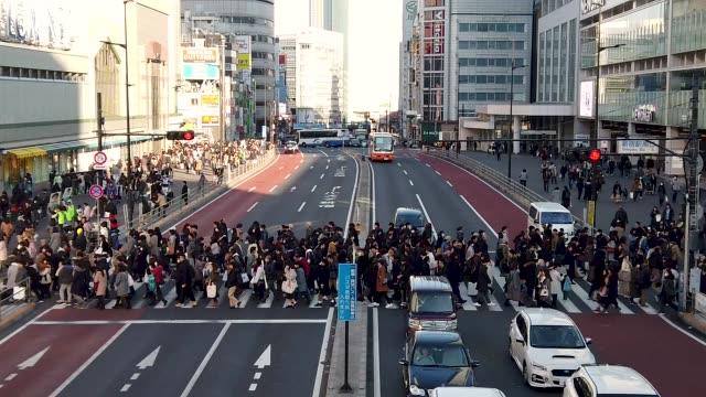 vídeos de stock, filmes e b-roll de câmera lenta de 4k. multidão de pessoas no cruzamento de estação de shinjuku em tóquio, japão. - cruzar