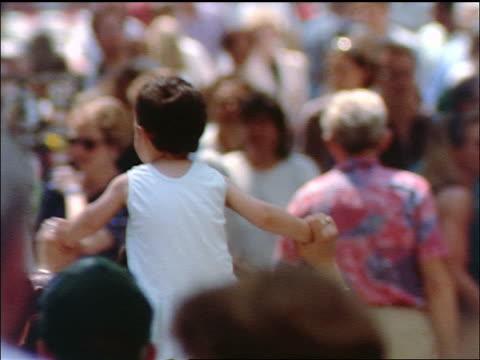 slow motion crowd of people walking in plaza / girl on shoulders of mother / wiesbaden, germany - wiesbaden stock-videos und b-roll-filmmaterial