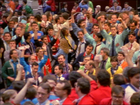 slow motion pan crowd of stock traders signal with hands / chicago board of trade or mercantile exchange - seller stock videos and b-roll footage