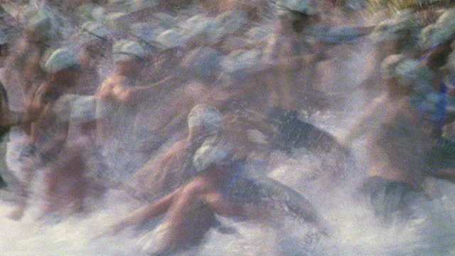 vídeos y material grabado en eventos de stock de slow motion pan crowd of swimmers running into water + starting to swim / iron man competition, hawaii - triatleta