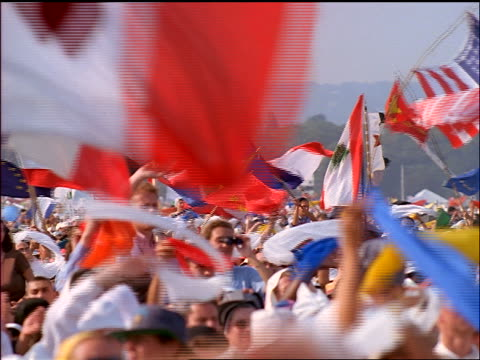 stockvideo's en b-roll-footage met slow motion crowd standing outdoors waving international flags - politieke bijeenkomst