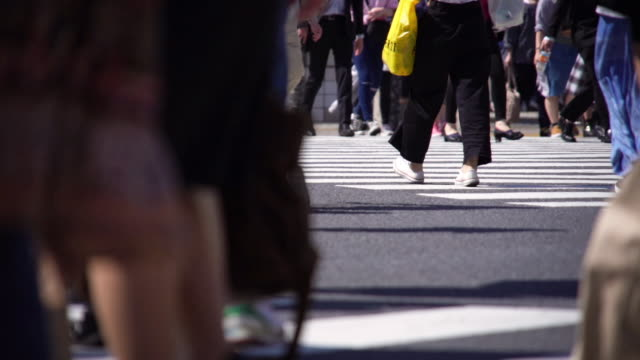 slow motion crowds of people walking on a crosswalk. - geographical locations stock videos & royalty-free footage