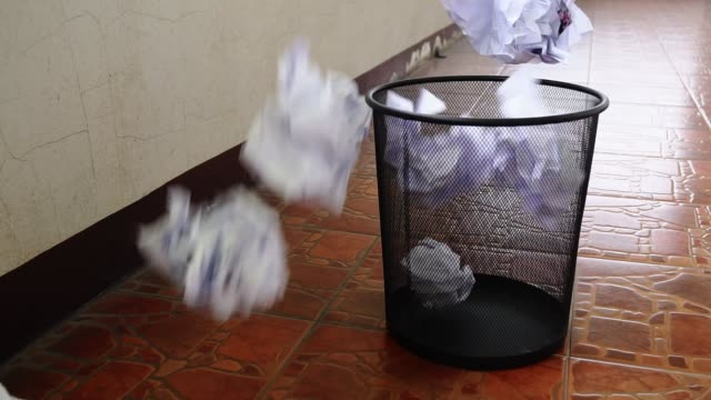 slow motion, crumpled paper recycle throw into black trash. - throwing stock videos & royalty-free footage