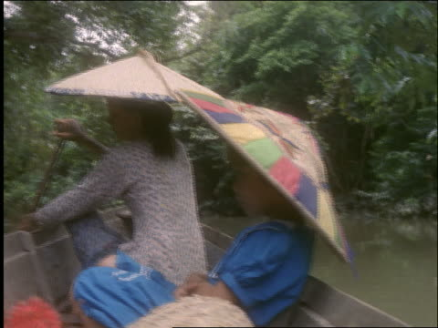slow motion pan of dayak woman + girl in canoe on river / rambutans / mahakkam river / borneo / indonesia - dayak stock videos and b-roll footage