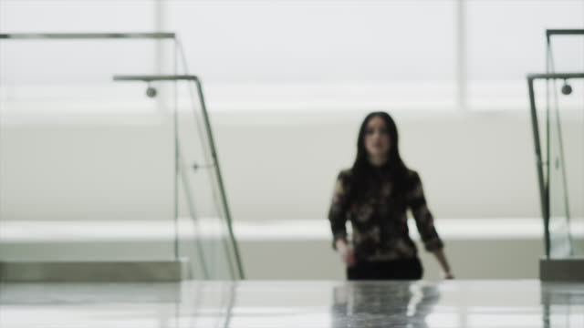 Slow motion defocused shot of businesswoman ascending stairs in office / Provo, Utah, United States,