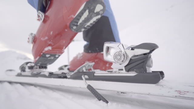 slow motion detail close up ski boot stepping in ski binding