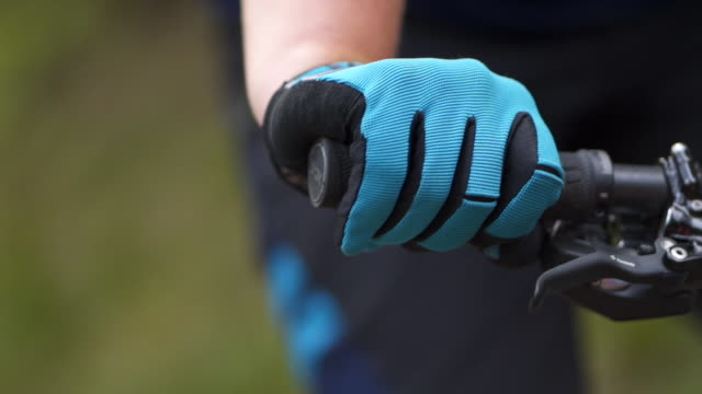 slow motion detail shot of a mountain bikers hand on handle bars - mountain bike stock videos & royalty-free footage