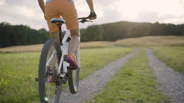 slow motion detail woman cycling on e mountain bike in rural landscape back view