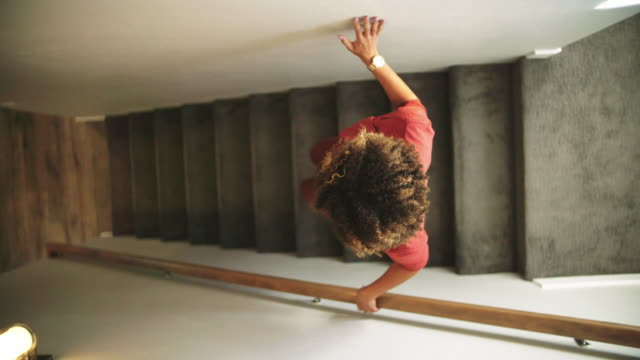 vídeos de stock e filmes b-roll de slow motion directly above shot of a woman of mixed race walking down carpeted stairs in a home, using the wall and a hand rail for support - escadaria