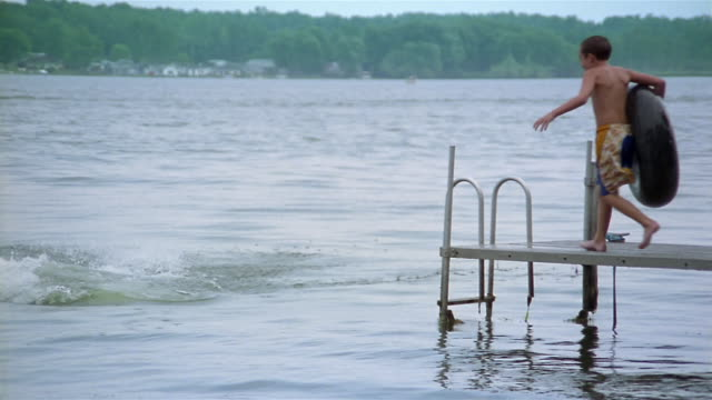 slow motion dog and two boys holding inner tubes jumping off pier into lake / silver lake, new york - stehendes gewässer stock-videos und b-roll-filmmaterial