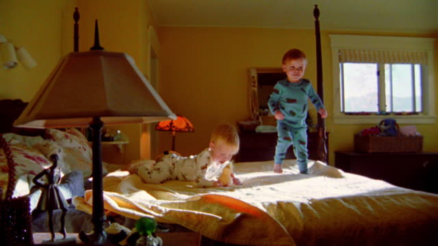 slow motion dolly shot around two blonde toddler boys in pajamas walking, falling + playing on large bed - geschwister stock-videos und b-roll-filmmaterial