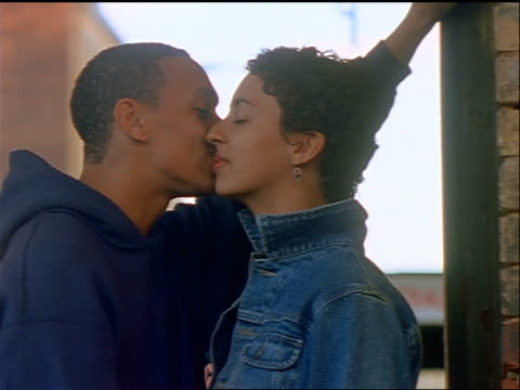 vidéos et rushes de slow motion dolly shot black teen couple leaning against wall kissing / nyc - couple d'adolescents
