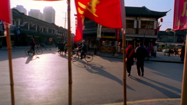 slow motion dolly shot city street with people on bicycles + red flags in foreground / Old Town, Shanghai, China