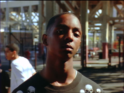 slow motion dolly shot close up PORTRAIT frowning Black male teen standing in outdoor basketball court / Brooklyn