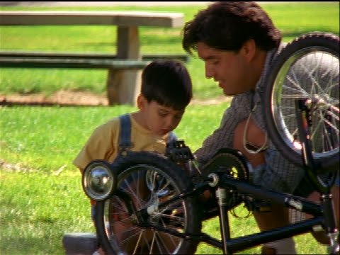 slow motion dolly shot hispanic man showing young boy how to repair bicycle outdoors - stabilisers stock videos & royalty-free footage