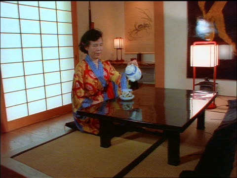 slow motion dolly shot in to middle-aged asian woman on tatami mat pouring tea + sipping it - tatami mat stock videos and b-roll footage
