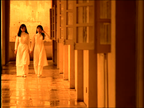 slow motion dolly shot of 2 women walking on veranda / Vietnam