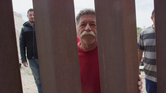 slow motion dolly shot of a hispanic man in his sixties with a mustache (on the mexican side) peeking through the steel-slat border wall between mexico and the united states with several other hispanic, male friends and a dog while the camera films them f - geographical border stock videos & royalty-free footage