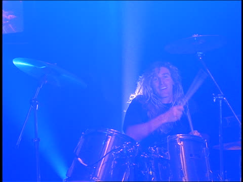 slow motion dolly shot of man with long hair playing drums in concert - moderne rockmusik stock-videos und b-roll-filmmaterial