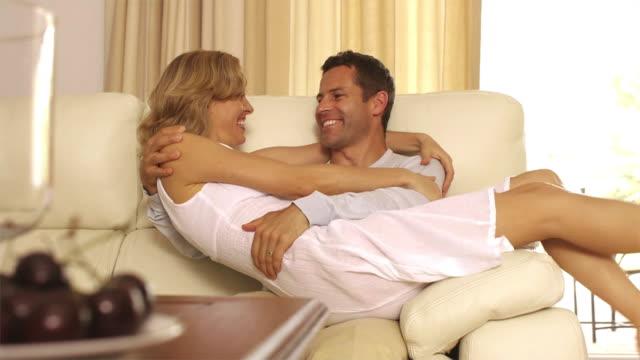 slow motion dolly shot of playful couple on couch/marbella region, spain - tre fjärdedels längd bildbanksvideor och videomaterial från bakom kulisserna