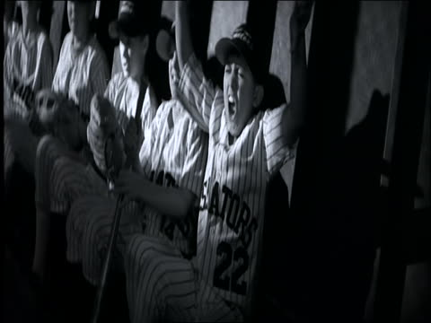 b/w slow motion dolly shot past boys in uniforms shouting + cheering in dugout / little league baseball - youth baseball and softball league stock videos and b-roll footage
