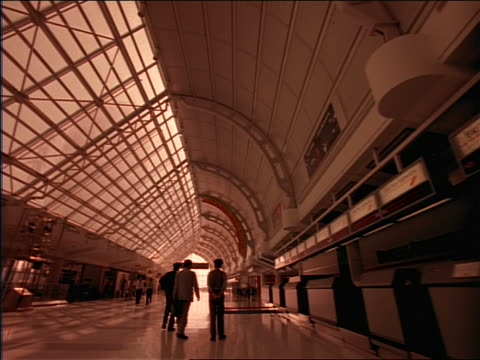 vídeos de stock, filmes e b-roll de slow motion dolly shot past empty ticket counters + people walking in airport terminal - ticket