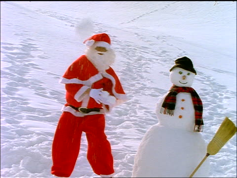 slow motion dolly shot santa claus standing next to snowman + throwing snowballs at camera - snowman stock videos & royalty-free footage