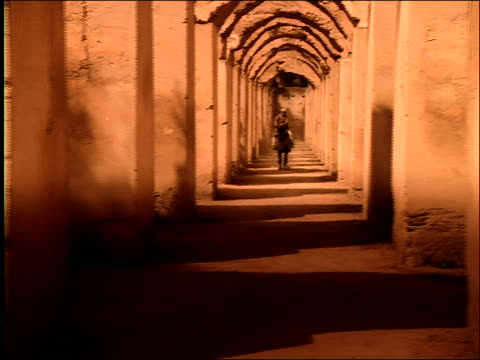 slow motion dolly shot to Middle Eastern man riding horse running toward camera in arched corridor / Morocco