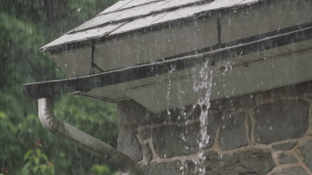 slow motion downpour as gutter overflows - overflowing stock videos & royalty-free footage