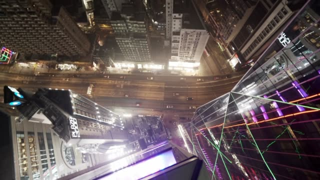 slow motion: downward pan of hong kong at night - ecke eines objekts stock-videos und b-roll-filmmaterial