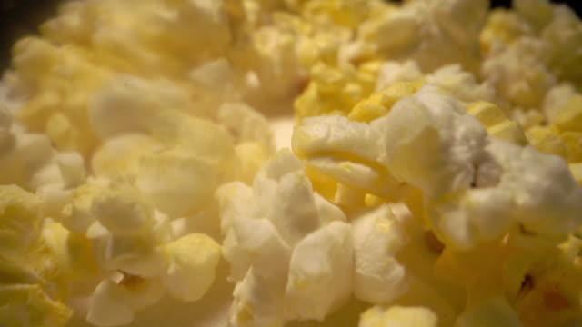 スローモーション下向きのスーパークローズアップ移動マクロ広角フレッシュバター脂っこい黄色ポップコーン - 塩味スナック点の映像素材/bロール