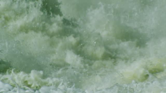 Slow motion dramatic water churning behind dam