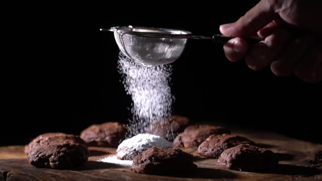 slow motion dressing one chocolate cookie with icing - ingredient stock videos & royalty-free footage