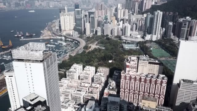 slow motion: drone pans along busy hong kong street to view of city and bay - causeway stock videos & royalty-free footage