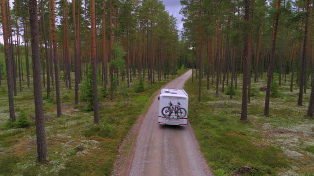 slow motion: drone shot of bicycle over camper van amidst trees in forest - smaland, sweden - camper van stock videos & royalty-free footage