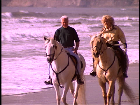 slow motion elderly couple riding horses on beach / hold hands