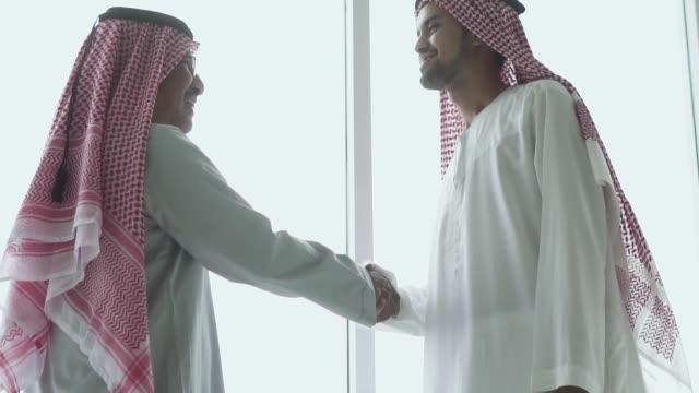 slow motion: emirati businessmen shaking hands - saudi arabia stock videos & royalty-free footage